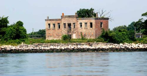 Civil War ruins on Hart Island surrounded by barbed wire.